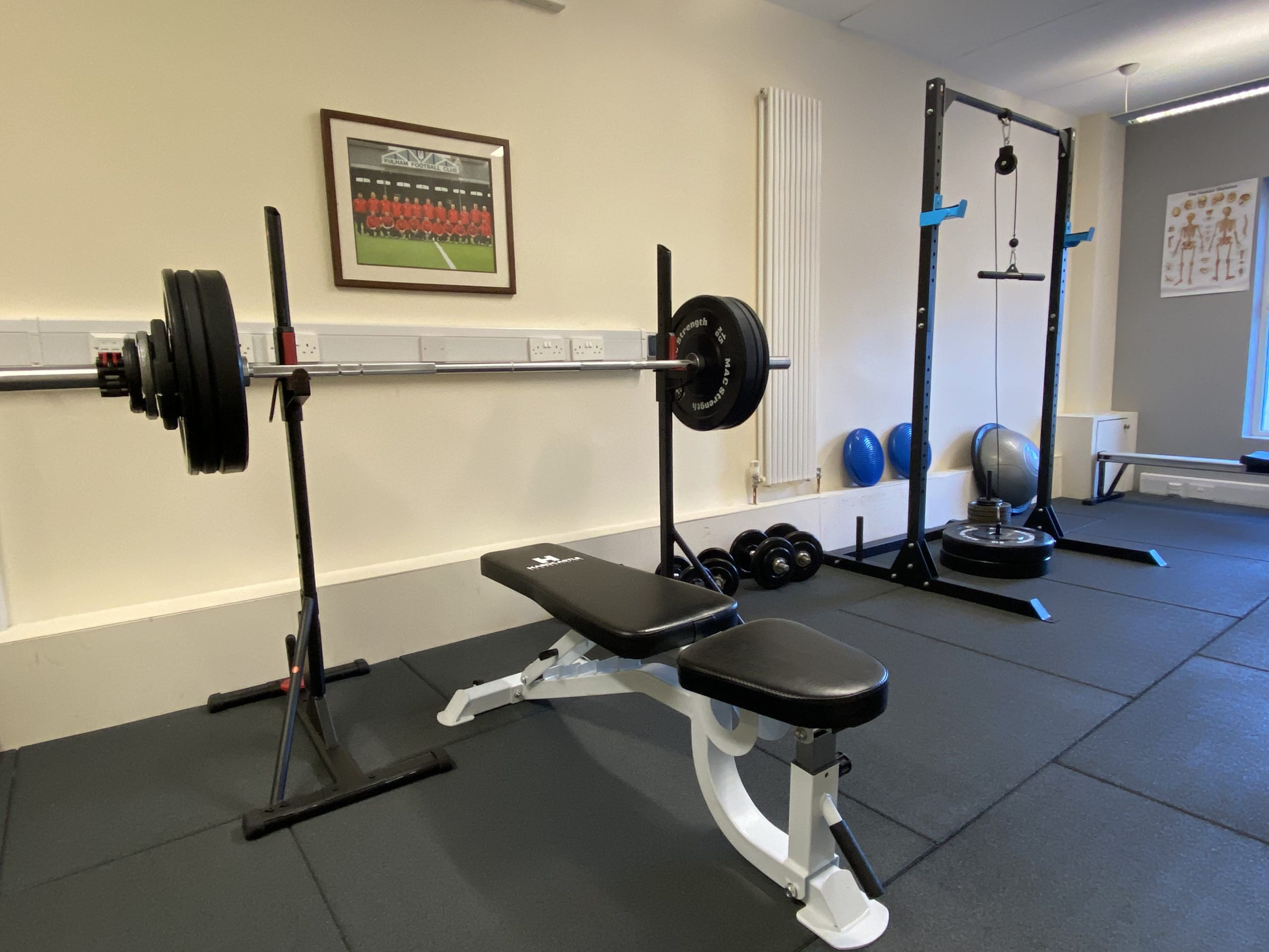 Bench press, squat rack and dumbbells in gym
