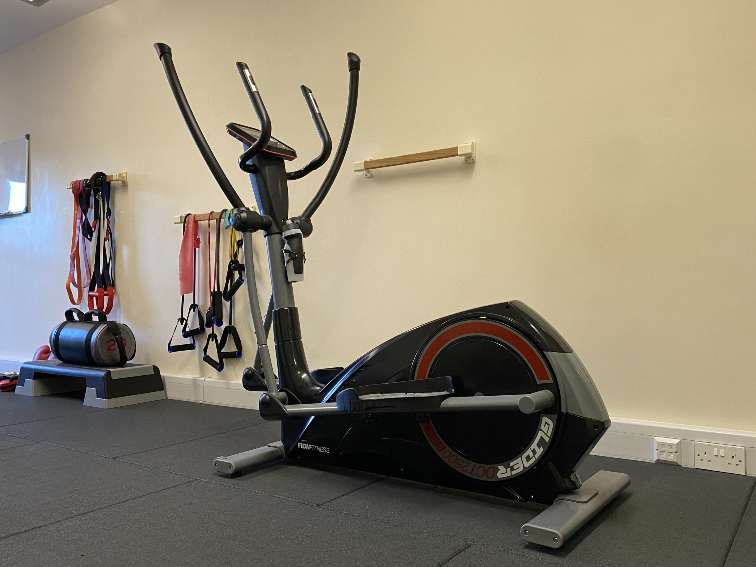 Elliptical cross trainer, resitance bands, step and power bag in gym