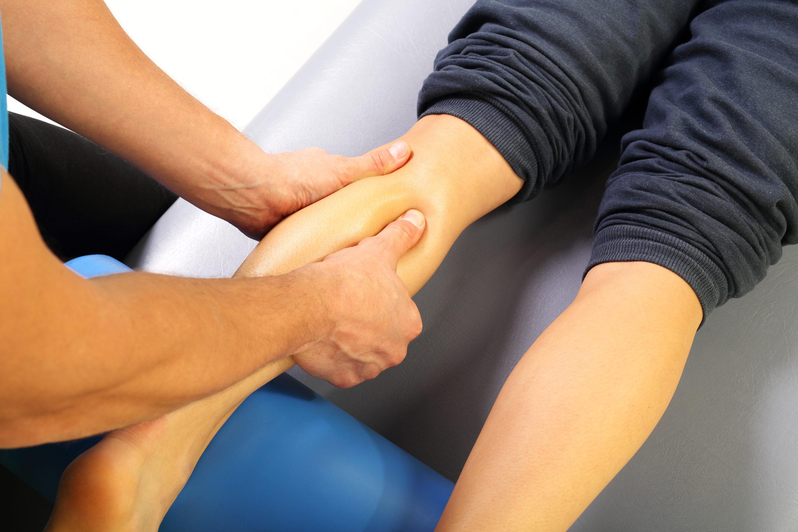 Physiotherapist using deep tissue massage to treat muscle soreness