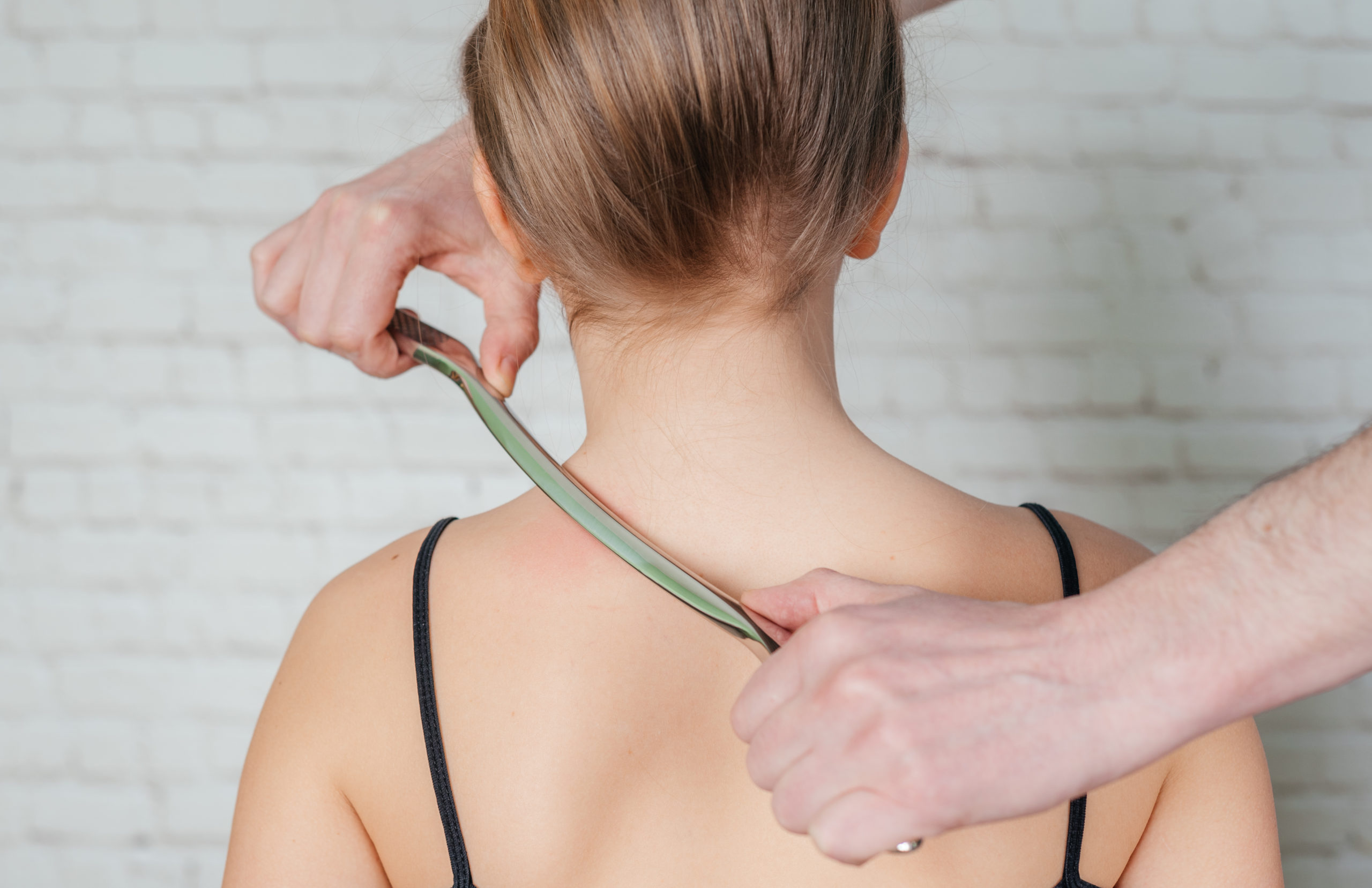 Physiotherapist treating a soft tissue injury to the shoulder and neck area